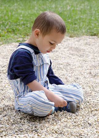 sitting on the ground: Child sitting on ground in a park playing with pebbles.