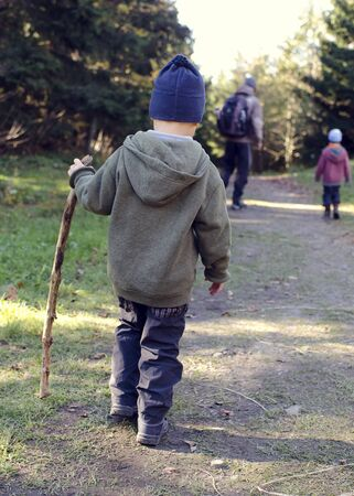 Child with stick walking on forest path at family hike, father other walkers in background, back view.