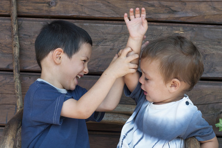 sibling rivalry: Two children boys, toddler and his older brother play fighting, concept of sibling rivalry Stock Photo