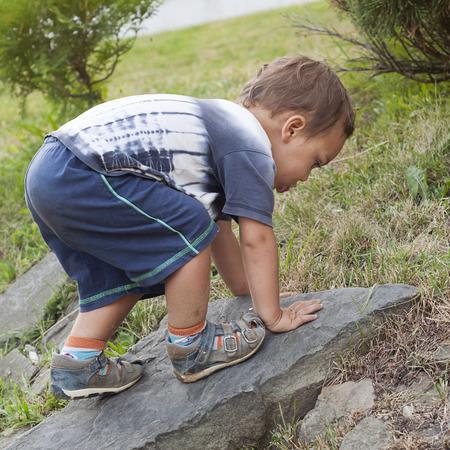 niño escalando: Todler niño que sube una roca en una naturaleza o en el jardín.