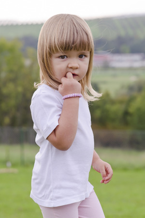 gir: Potrait of a cut child gir with a finger in her mouth biting her nail standing in park or garden in summer. Stock Photo