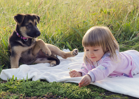 Child girl with puppy dog relaxing on blanket in grass at nature meadow.