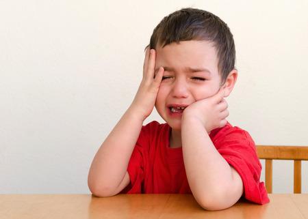 不幸な怒って、泣いている子供の少年のポートレート