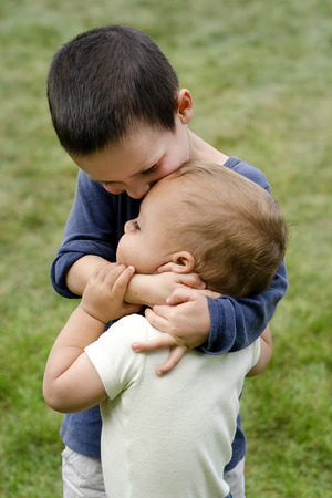 brother sister fight: Two children, siblings, small boys, playing together outdoors; the older brother is holding the younger child around his neck, hugging and kissing him.