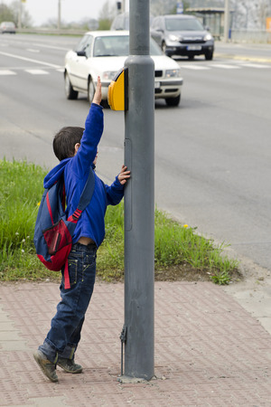 School child boy pressing a button on pedestrian crossing, car traffic in the background. Stock Photo