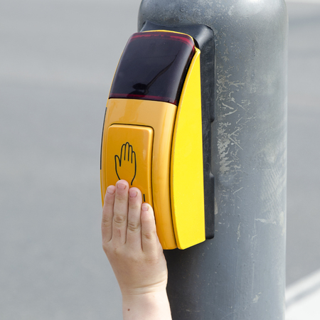 crossing fingers: Deatil of a child hand pressing the button on pedestrian crossing. Stock Photo