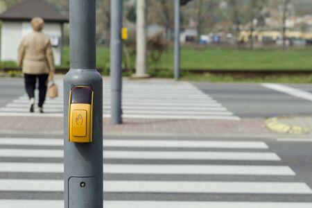 semaforo peatonal: Mujer de la parte posterior en la calle peatonal que cruza con la cebra y el pulsador.
