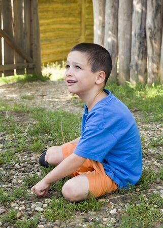 sitting on the ground: Child sitting on ground in garden