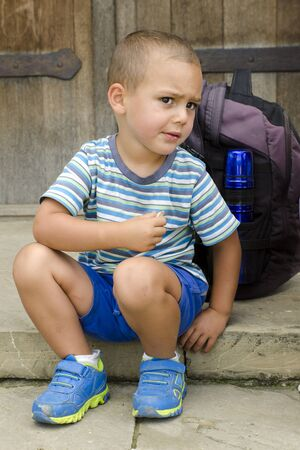 snacking: Child sitting on a step outside, snacking and resting during a walk trip or trek.