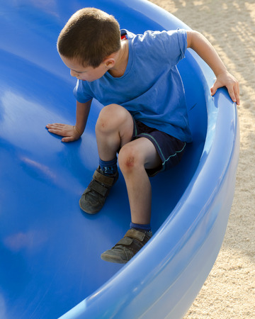 Child boy on a blue slide in children playground, top view.