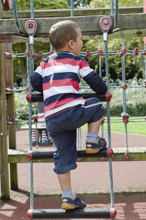 climbing ladder: Child playing at children playground, climbing the  rope ladder.