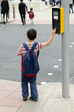 semaforo peatonal: Un muchacho niño de pie sobre un pavimento o una acera empujando el botón en las señales de tráfico para el paso de peatones, el concepto de la seguridad vial.