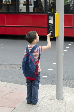 niño empujando: Un muchacho niño de pie sobre un pavimento o una acera empujando el botón en las señales de tráfico para el paso de peatones, el concepto de la seguridad vial.