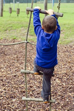 niño escalando: Niños jugando en parque infantil, subir la escalera de cuerda.