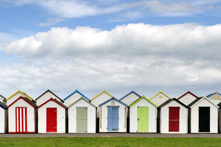 Row of colorful wodden beach huts, typical at english seaside. Фото со стока