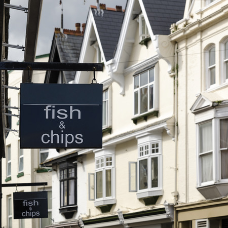 Fish and chips shop sign on a building at street of houses in England.