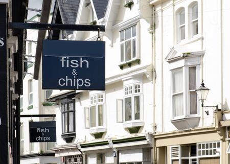 fish shop: Fish and chips sign on a building at street of houses in England.