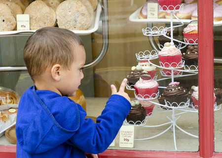 golosinas: Niño que mira a través de la ventana en dulce pastelería o panadería apuntando a las tortas.