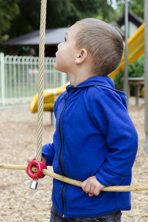 rope ladder: Child playing at children playground, looking up at rope ladder.