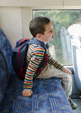 transporte escolar: Niño con mochila escolar que viaja en un autobús de la ciudad en transporte público.