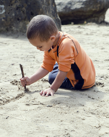 sand writing: Child of preschool age drawing into sand with wood stick