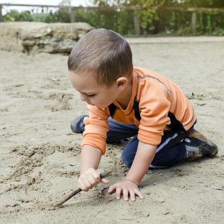 terreno: Bambino di età prescolare disegno in sabbia con bastone di legno
