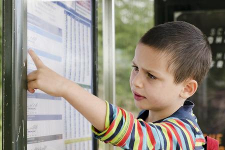 parada de autobus: Muchacho del ni�o que lee un calendario en una parada de autob�s.