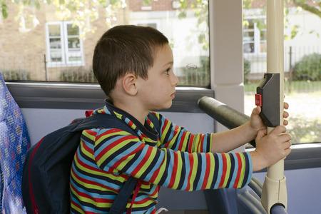 停止ボタンを押すと公共交通機関バスのスクール バッグを持つ子供。 写真素材
