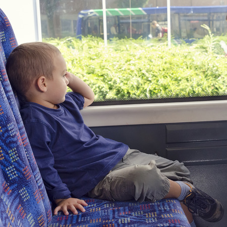 Child  travelling on a public transport city bus .