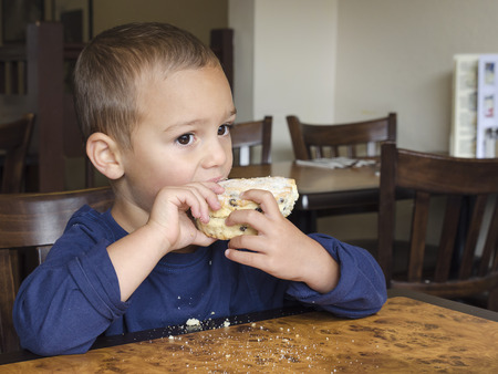 Child eating rock cake in a cafe.