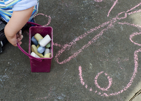 Child hand with box of color chalks and chalk  drawing on a street. photo