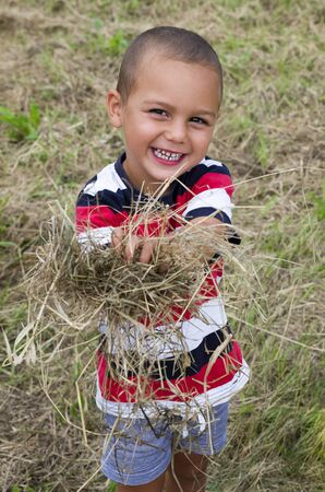 Portrait of a happy smiling child boy holding and armful of dry hay or straw.