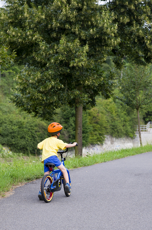 Child cycling on a cycle path along a river in summer, back view.