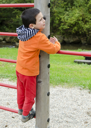 Child playing on a climbing frame at children playground at park. Stock Photo