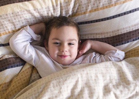 Sleepy happy child lying in a bed, waking up in the morning.