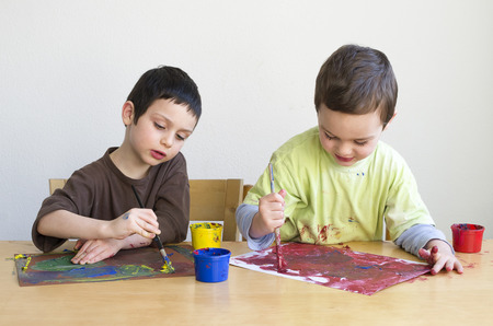 Child boy painting a picture with brush at home or school playgroup. Stock Photo