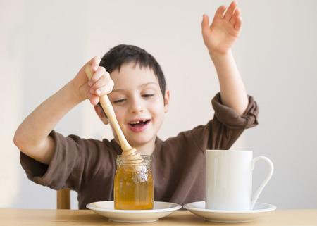 Happy child boy adding honey into a cup of tea
