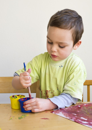 Child boy painting a picture with brush at home or school nursery.