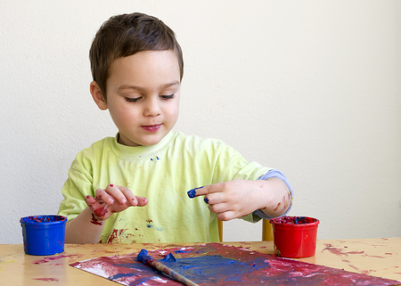Child boy painting a picture with with finger colors at home or school nursery.