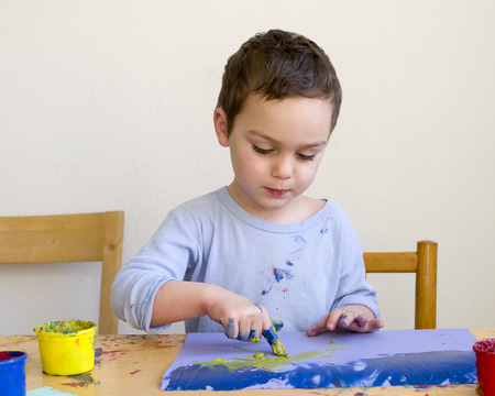 children painting: Child boy painting a picture with with finger colors at home or school nursery.