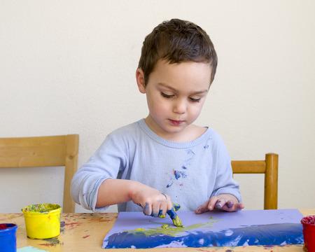 Muchacho del niño pinta un cuadro con los colores de los dedos en el hogar o la guardería.