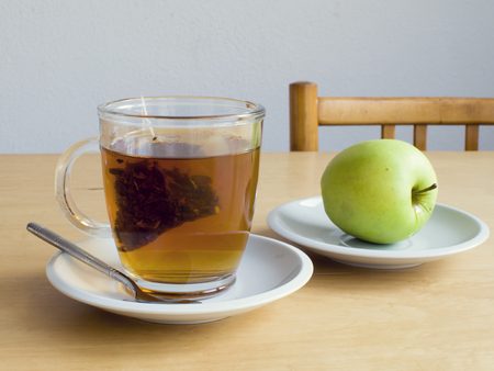 Cup of tea with teabag and a green apple on a plate on table, snack time.