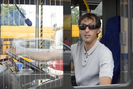 Male bus driver driving a citý public service bus Stock Photo