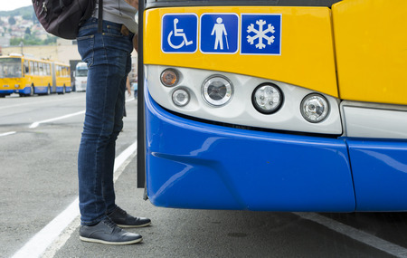 Detail of a modern city public transport  bus and a passanger getting on.