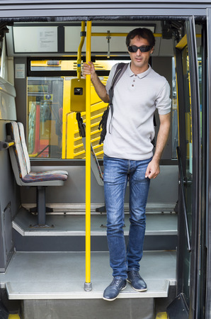 on off: Male passenger getting off the public service city bus Stock Photo
