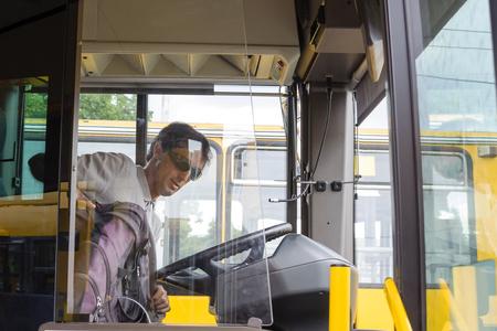 public service: Male bus driver getting ready to drive a city public service bus