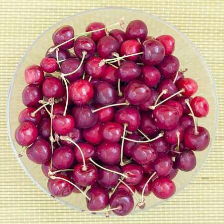 Red cherries fruit in a glass bowl, top view. Stock Photo