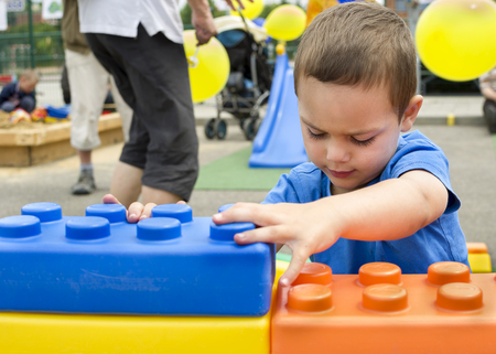 ouside: Child boy playing with large building block at  outdoor public playground
