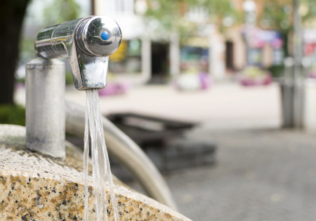 Drinking water tap fountain on a city square with running water Stock Photo