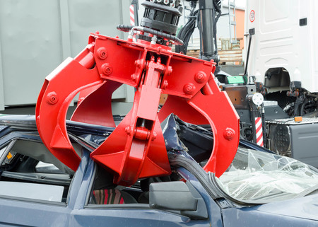 車のスクラップのヤードでリサイクルのために古い車をつかんで産業クレーンの爪のディテール。